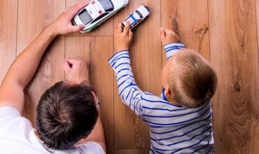 Kid with father playing with toycar | Flooring Concepts